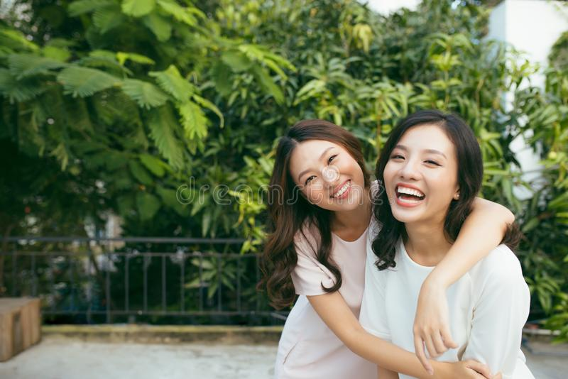 Beauties in style. Two beautiful young well-dressed women smiling at camera while standing embracing outdoors.  stock photos