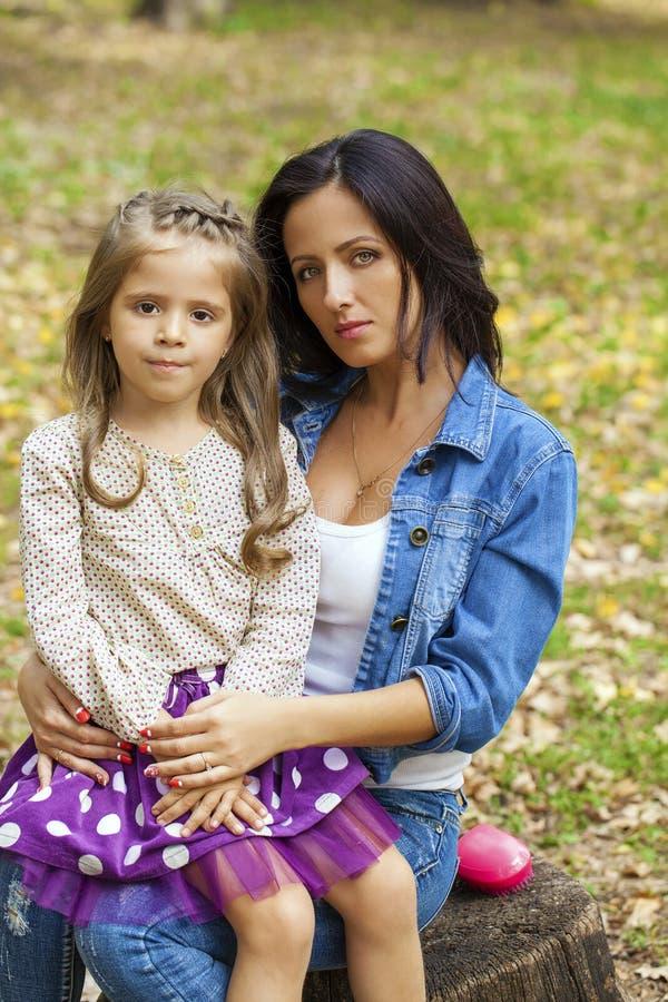 Beautifal小女孩和愉快的母亲在秋天停放 免版税库存图片