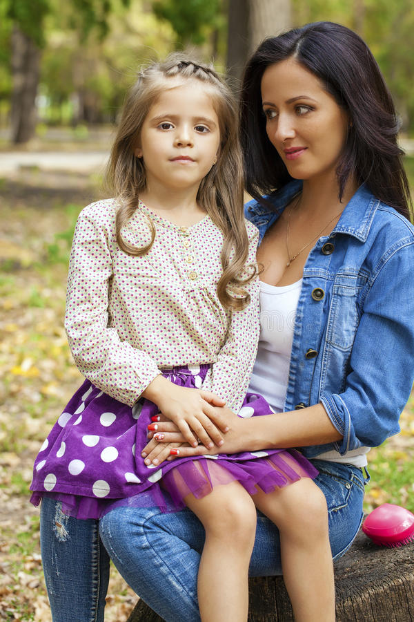 Beautifal小女孩和愉快的母亲在秋天停放 免版税库存照片