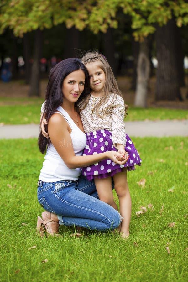 Beautifal小女孩和愉快的母亲在秋天停放 库存图片