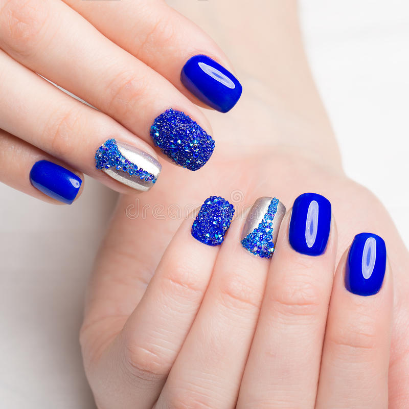 Beautifil blue manicure with rhinestone. Nail Design. Close-up.  royalty free stock image