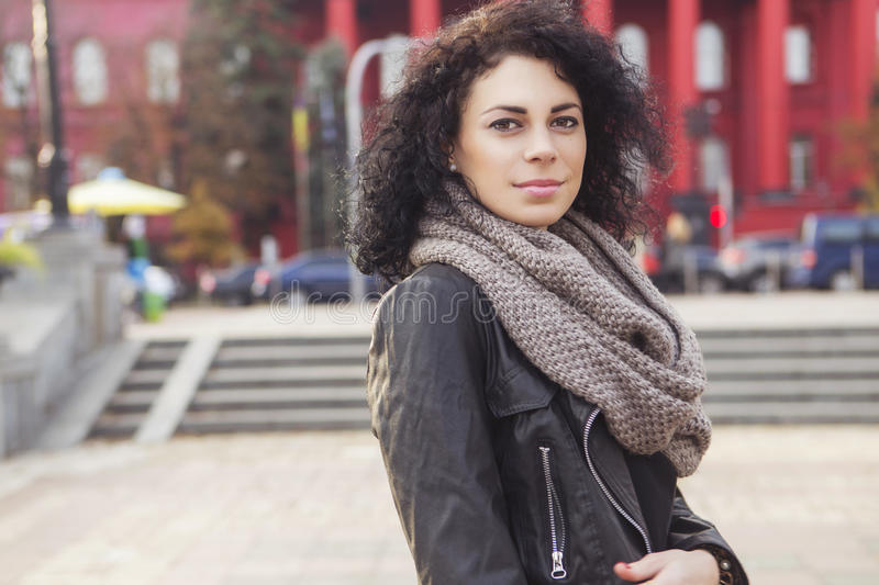 Beautifil brunette caucasian woman in leather jacket and scarf w stock photography