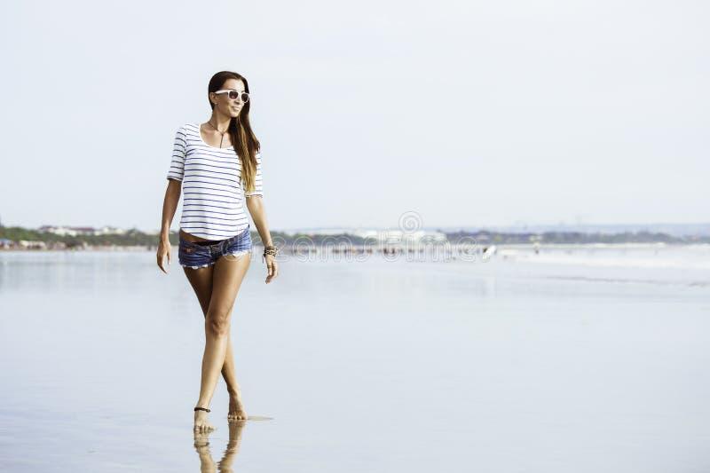 Beautifil młoda kobieta z odprowadzeniem wzdłuż plaży obraz stock