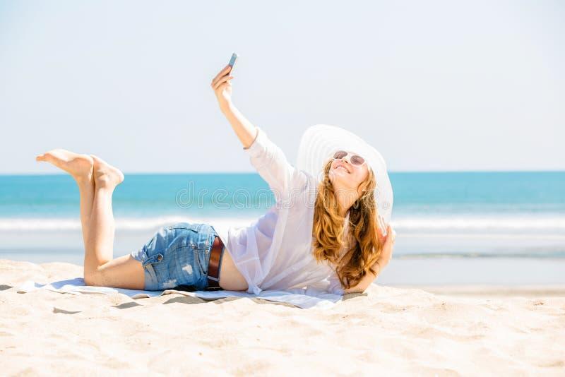Beautifil młodej kobiety lying on the beach na plaży przy pogodnym zdjęcia royalty free