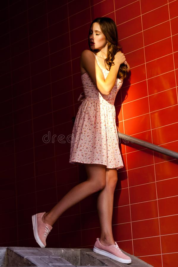 Beautifil young adult brunette standing on stairs and straw falls on her face royalty free stock photo
