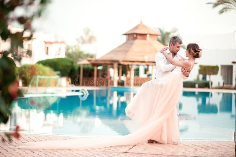 BeautifNewly在婚姻以后已婚夫妇在豪华旅游胜地 浪漫新娘和新郎松弛近的游泳池 免版税库存图片