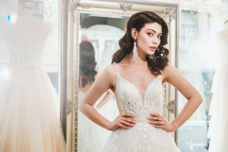 Beautifu-Braut, die Hochzeitskleid in einem Heiratssalon w?hlt stockfoto