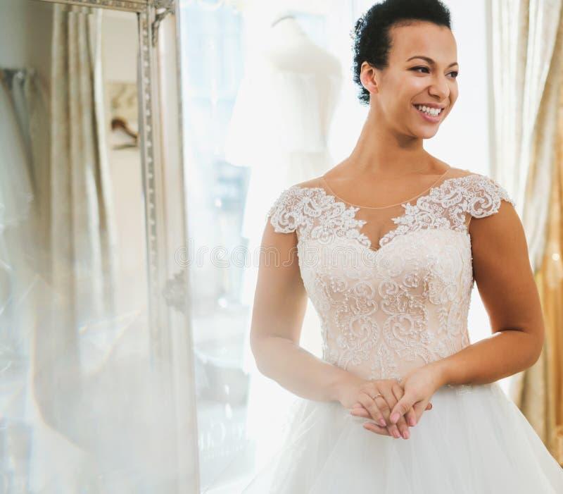 Beautifu-Braut, die Hochzeitskleid in einem Heiratssalon w?hlt stockfotografie