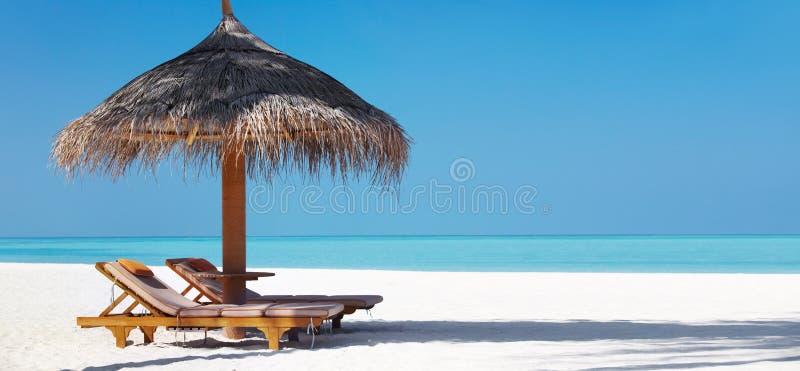 Beautifu Strand mit Stühlen und Regenschirm lizenzfreie stockbilder