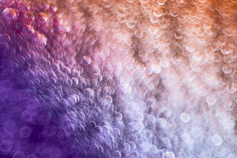 Beautiful abstract blurred bokeh on violet and orange background. For decoration design stock photo