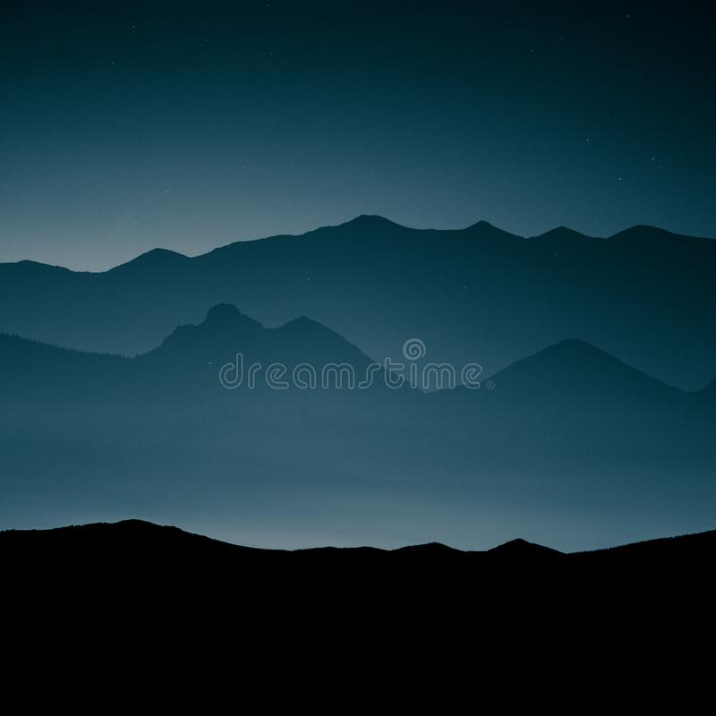 A beautiful, abstract monochrome mountain landscape in blue tonality. stock images