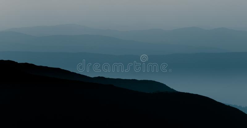 A beautiful, abstract monochrome mountain landscape in blue tonality. Decorative, artistic look in black and white style royalty free stock photos
