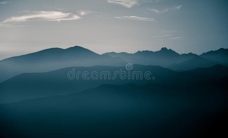 A beautiful, abstract monochrome mountain landscape in blue tonality. Decorative, artistic look in black and white style stock photos