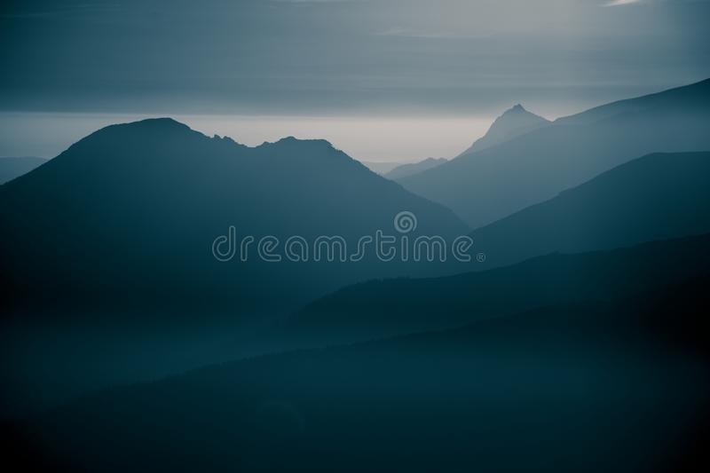 A beautiful, abstract monochrome mountain landscape in blue tonality. Decorative, artistic look in black and white style stock photography