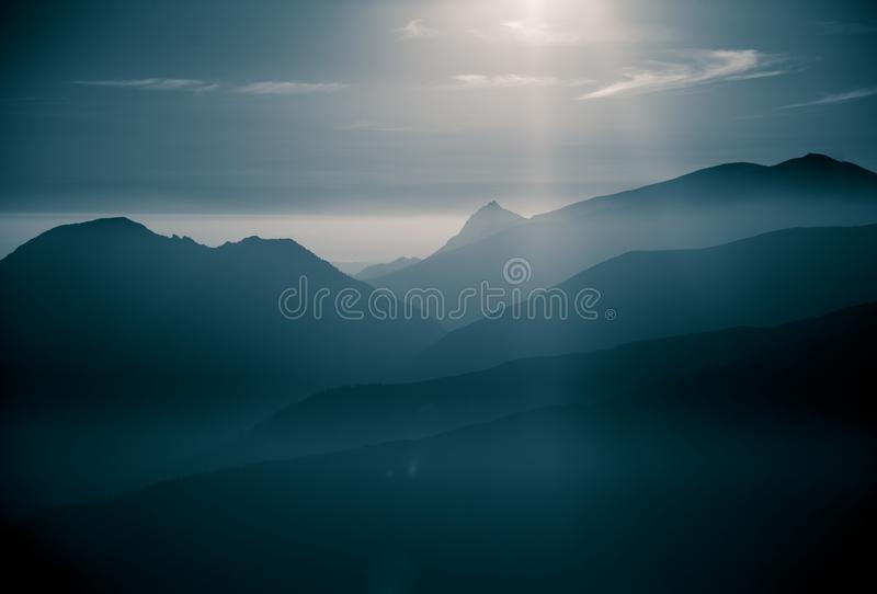 A beautiful, abstract monochrome mountain landscape in blue tonality. Decorative, artistic look in black and white style stock image