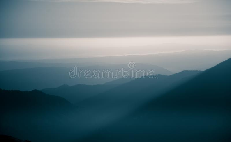 A beautiful, abstract monochrome mountain landscape in blue tonality. Decorative, artistic look in black and white style stock photo
