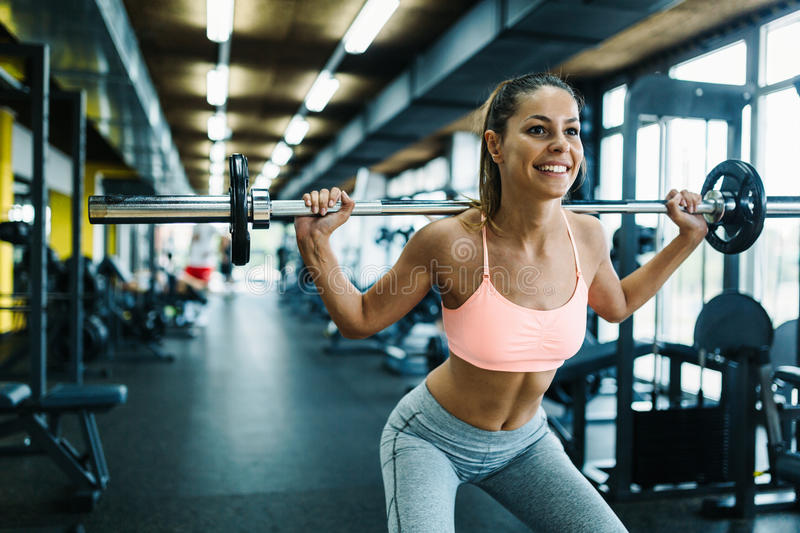 Beautiful active woman doing squats in gym stock photography