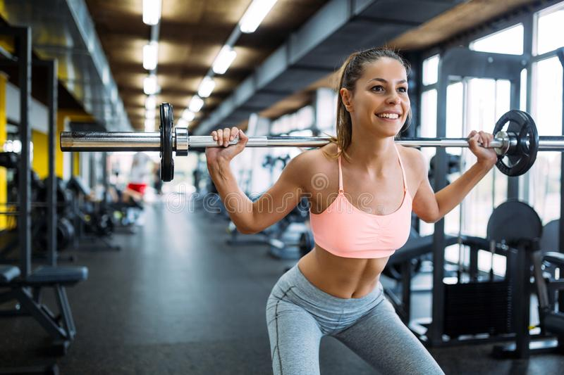 Beautiful active woman doing squats in gym stock photos