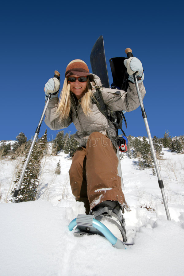 Beautiful active woman with snowshoes and snowboard royalty free stock photography