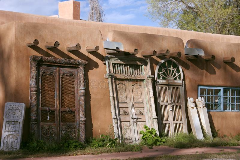 Beautiful adobe house where the sells antic doors in Sante Fe, New Mexico. Adobe house with the characteristic plastered exterior in beautiful earth red color stock photos
