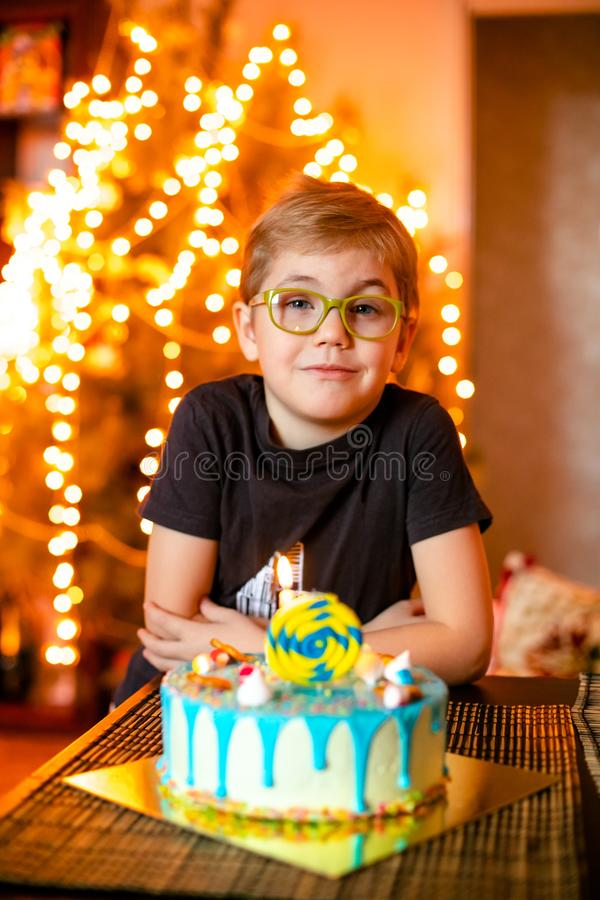 Beautiful adorable seven eight year old boy in grey shirt, celebrating his birthday, blowing candles on homemade baked cake, royalty free stock photo