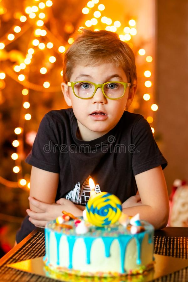 Beautiful adorable seven eight year old boy in grey shirt, celebrating his birthday, blowing candles on homemade baked cake, stock image