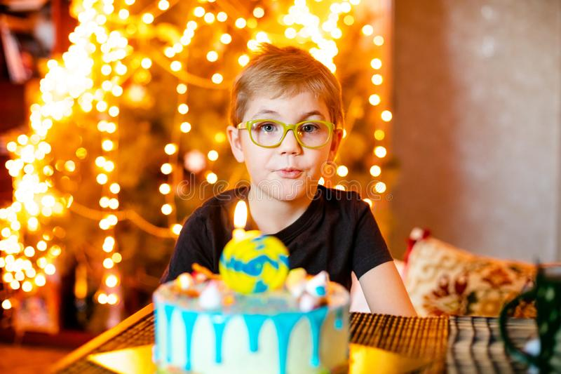 Beautiful adorable seven eight year old boy in grey shirt, celebrating his birthday, blowing candles on homemade baked cake, stock photos