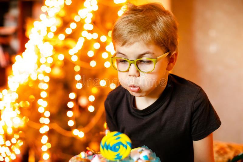 Beautiful adorable seven eight year old boy in grey shirt, celebrating his birthday, blowing candles on homemade baked cake, stock photo
