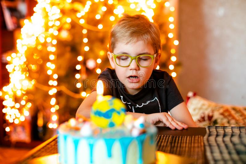 Beautiful adorable seven eight year old boy in grey shirt, celebrating his birthday, blowing candles on homemade baked cake, royalty free stock image