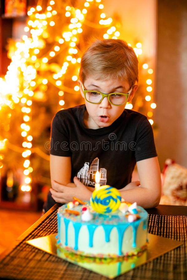 Beautiful adorable seven eight year old boy in grey shirt, celebrating his birthday, blowing candles on homemade baked cake, royalty free stock photos