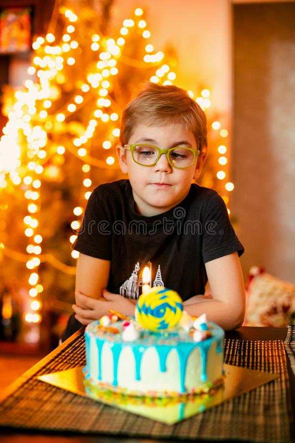 Beautiful adorable seven eight year old boy in grey shirt, celebrating his birthday, blowing candles on homemade baked cake, stock images