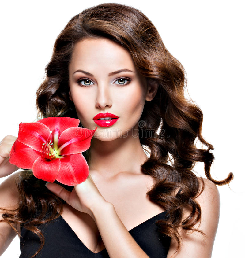 Beautiful adult girl with bright red lips and flower near the fa. Portrait of young beautiful adult girl with bright red lips and flower near the face - isolated royalty free stock photo
