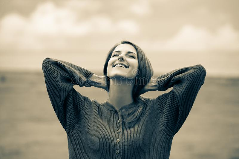 Beautiful adult girl in sweater at wheat field. And cloudscape on background. Image in sepia color style stock photos