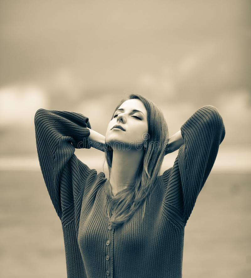 Beautiful adult girl in sweater at wheat field. And cloudscape on background. Image in sepia color style stock photography