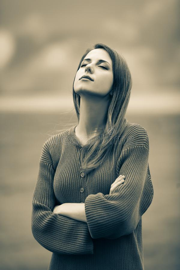 Beautiful adult girl in sweater at wheat field. And cloudscape on background. Image in sepia color style royalty free stock photos