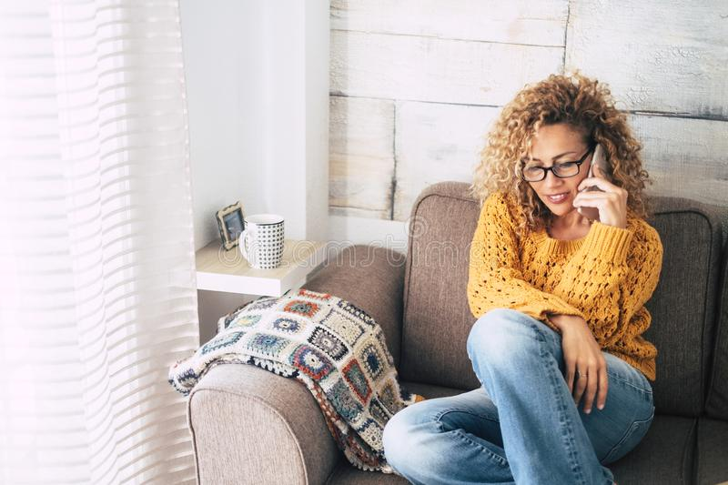 Beautiful adult people having phone call at home -curly caucasian blonde woman sitting on the sofa with cellular -  Middle age. Beautiful adult people having royalty free stock photography