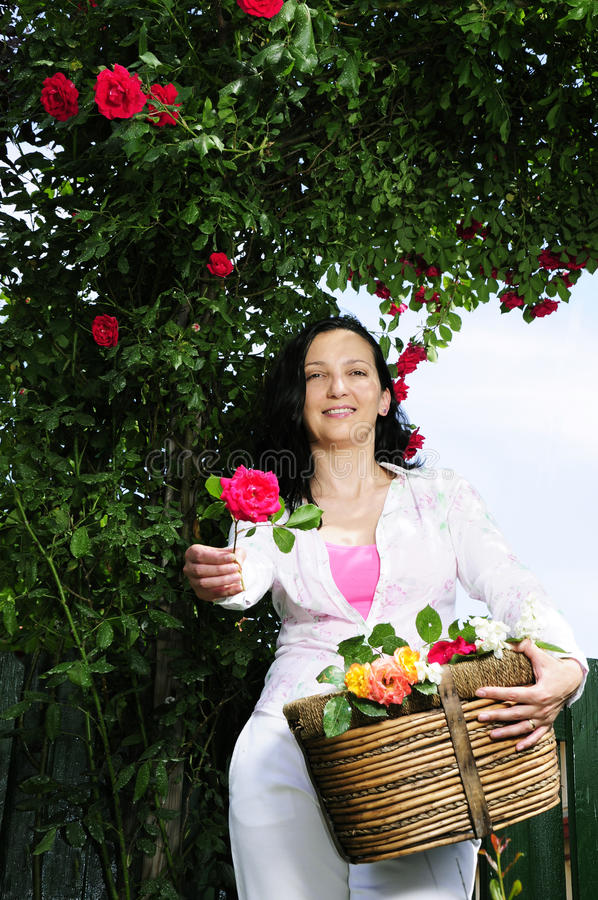 Beautiful adult woman giving a rose in garden