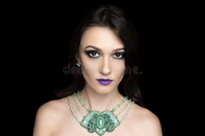Beautiful adult woman, green jewelry, hairstyle stock photos
