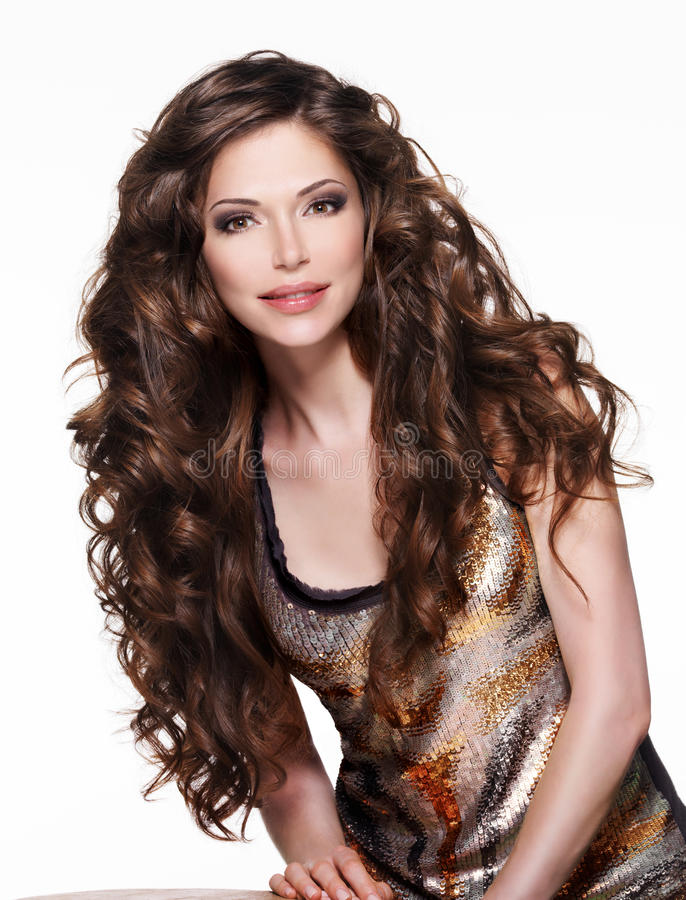 Beautiful adult woman with long brown curly hair. Fashion model over white background stock photos