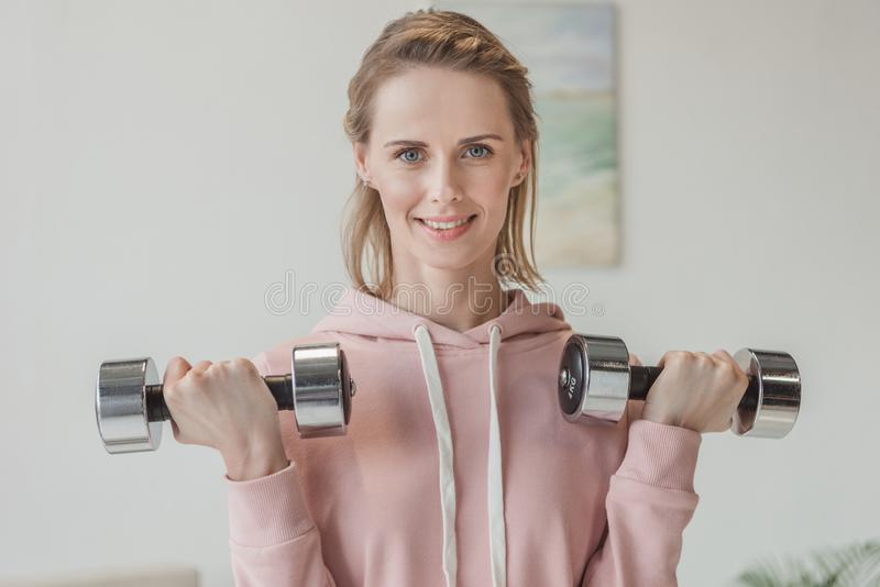 beautiful adult woman working out with dumbbells royalty free stock image