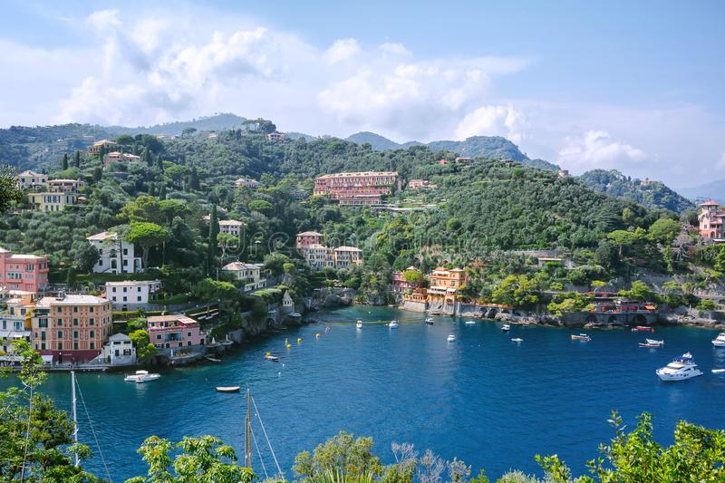 Beautiful aerial daylight view from top to boats on water, colorful houses and villas in Portofino town of Italy. Tourists walking on sidewalk stock image