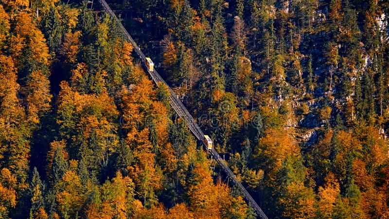 Beautiful aerial fall view of cable car ropeway funicular in austrian alps. Red cable railway car in the mountains. By resort village Hallstatt, Salzkammergut stock photos