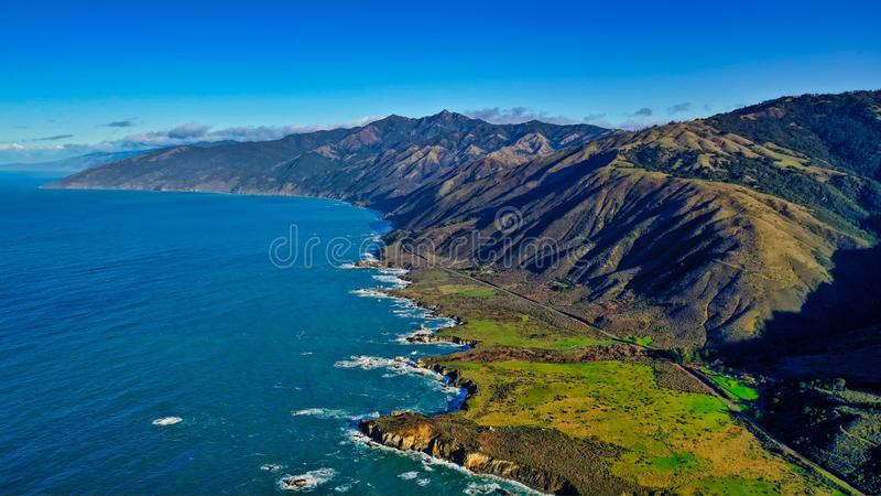 Beautiful aerial shot of the coast of the sea with green leaves and cloudy amazing sky stock image