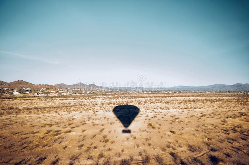 Beautiful aerial shot of a desert field with the shadow of a moving air balloon in the sky royalty free stock images