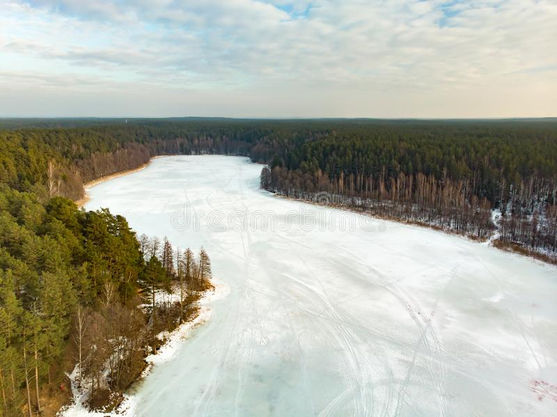 Beautiful aerial view of ice covered Balzis lake. Snowy pine forests surrounding a small lake. Scenic winter landscape near stock photo