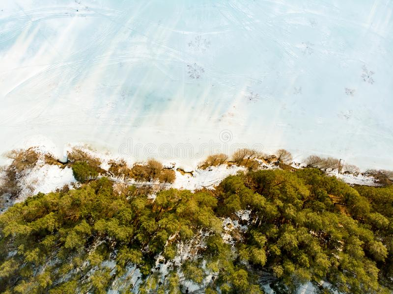 Beautiful aerial view of ice covered Balzis lake. Snowy pine forests surrounding a small lake. Scenic winter landscape near royalty free stock images