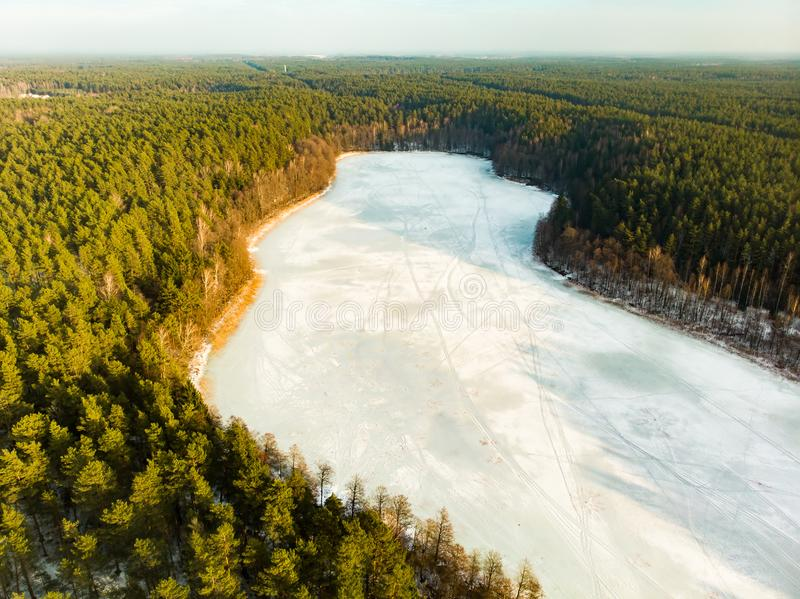 Beautiful aerial view of ice covered Balzis lake. Snowy pine forests surrounding a small lake. Scenic winter landscape near stock photography