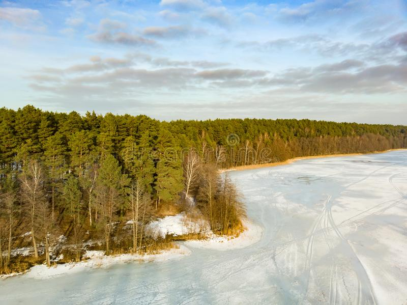 Beautiful aerial view of ice covered Balzis lake. Snowy pine forests surrounding a small lake. Scenic winter landscape near stock image