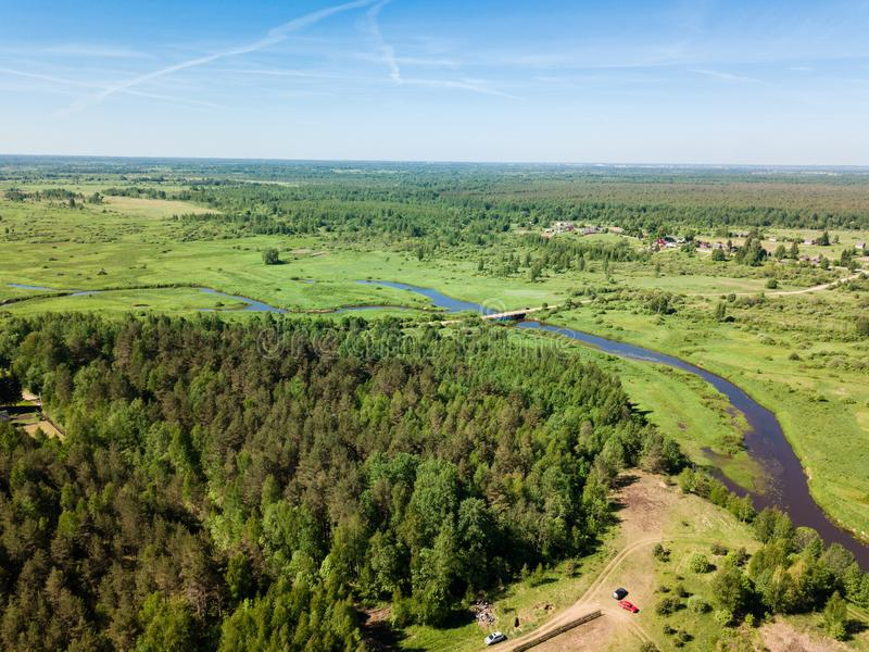 Beautiful aerial view of meandering river with bright green field and bottom-land meadow on summer day stock image