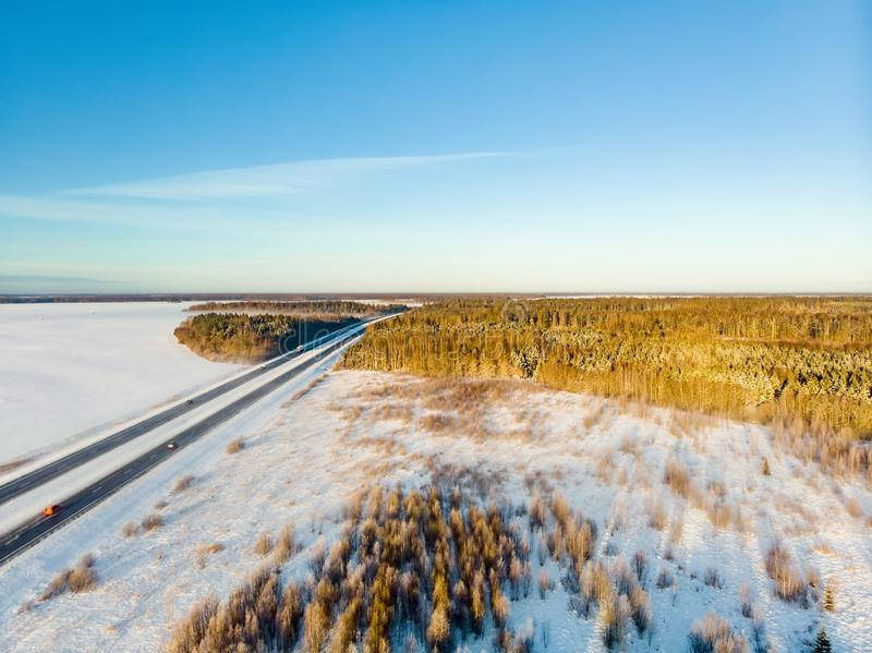 Beautiful aerial view of snow covered fields with a two-lane road among trees. Scenic winter landscape near Vilnius, Lithuania royalty free stock photography